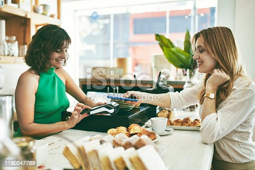 Hispanic female barista and customer performing mobile payment for coffee and baked pastries at Buenos Aires cafe.