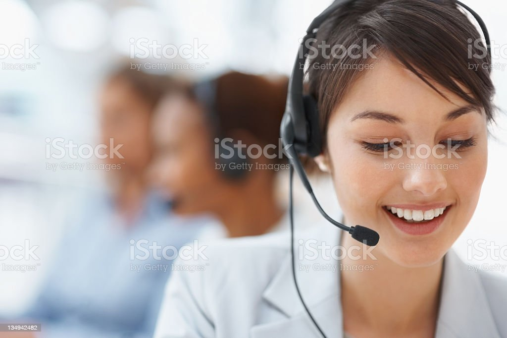 Smiling call center employee during a telephone conversation royalty-free stock photo