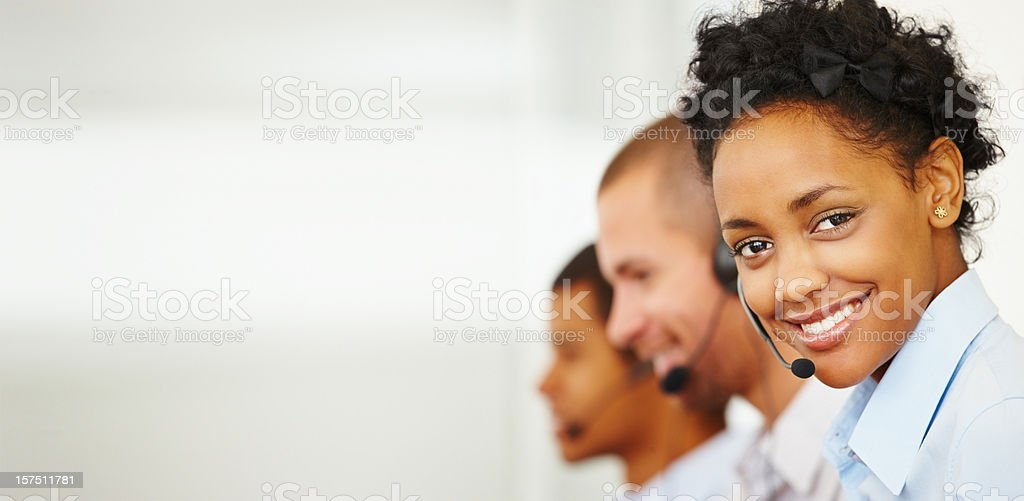Smiling call center employee with two colleagues behind her stock photo
