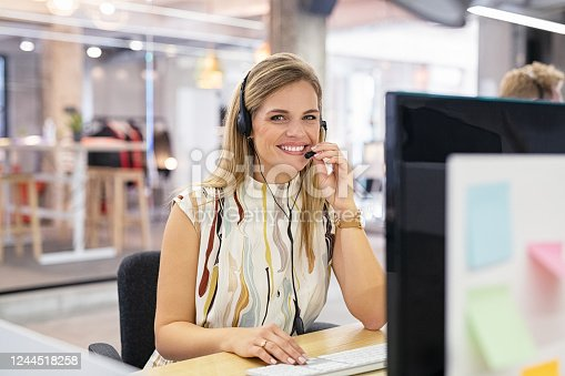 Smiling mid woman working as customer support operator with headset in a call center. Portrait of happy sales agent sitting at desk in modern office and looking at camera. Customer care and support service representative.