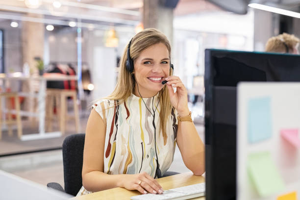 Smiling call center operator at desk stock photo