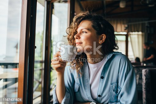 Smiling calm young woman drinking coffee looking out the window sitting at table in restaurant.