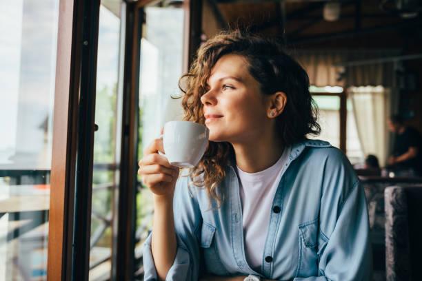 leende lugn ung kvinna dricker kaffe - kaffe bildbanksfoton och bilder