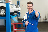 istock Smiling car mechanic holding tire jack and giving thumbs up 467694576