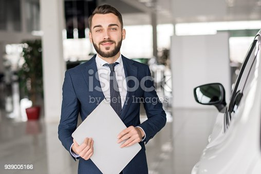 istock Smiling Car Salesman in Showroom 939005166