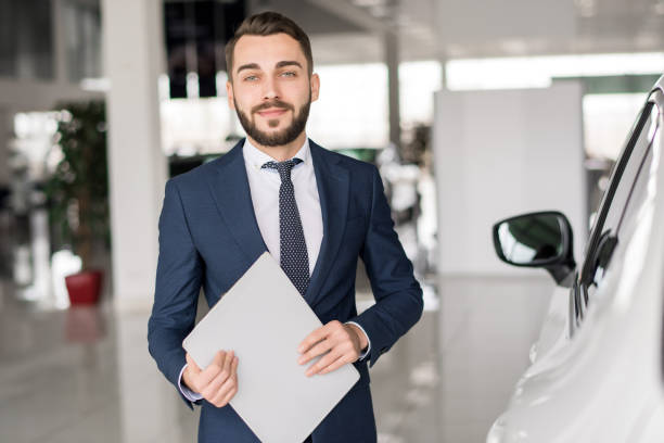 Smiling Car Salesman in Showroom Waist up portrait of handsome car salesman looking at camera  and smiling holding clipboard standing in luxury dealership showroom salesman stock pictures, royalty-free photos & images