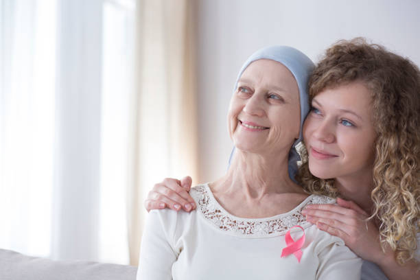 Smiling caregiver hugging senior woman Smiling caregiver hugging senior woman with cancer and pink ribbon chemotherapy cancer stock pictures, royalty-free photos & images