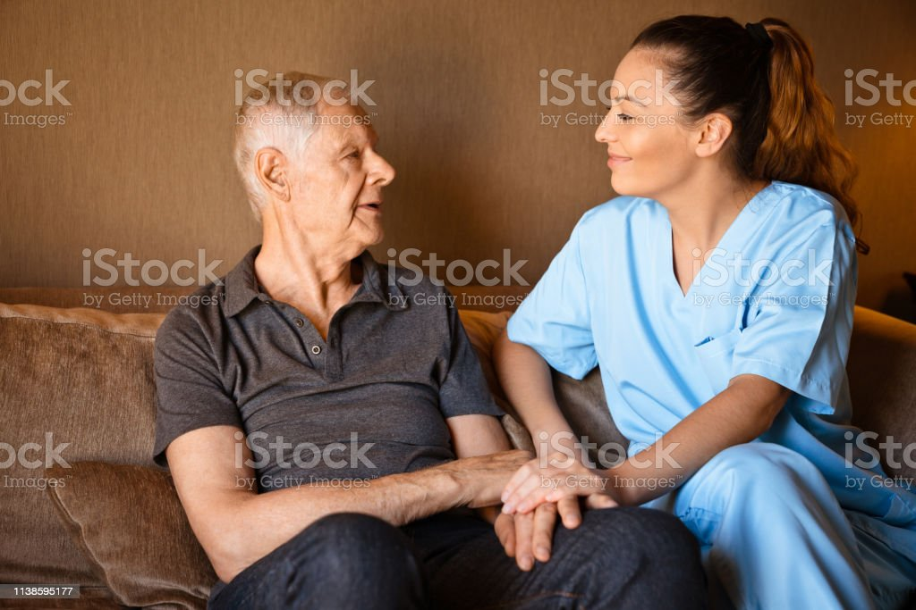 Smiling mid adult caregiver talking to senior man. Male and female...