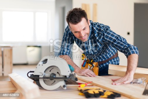 istock Smiling carpenter checking result of his work 485163923