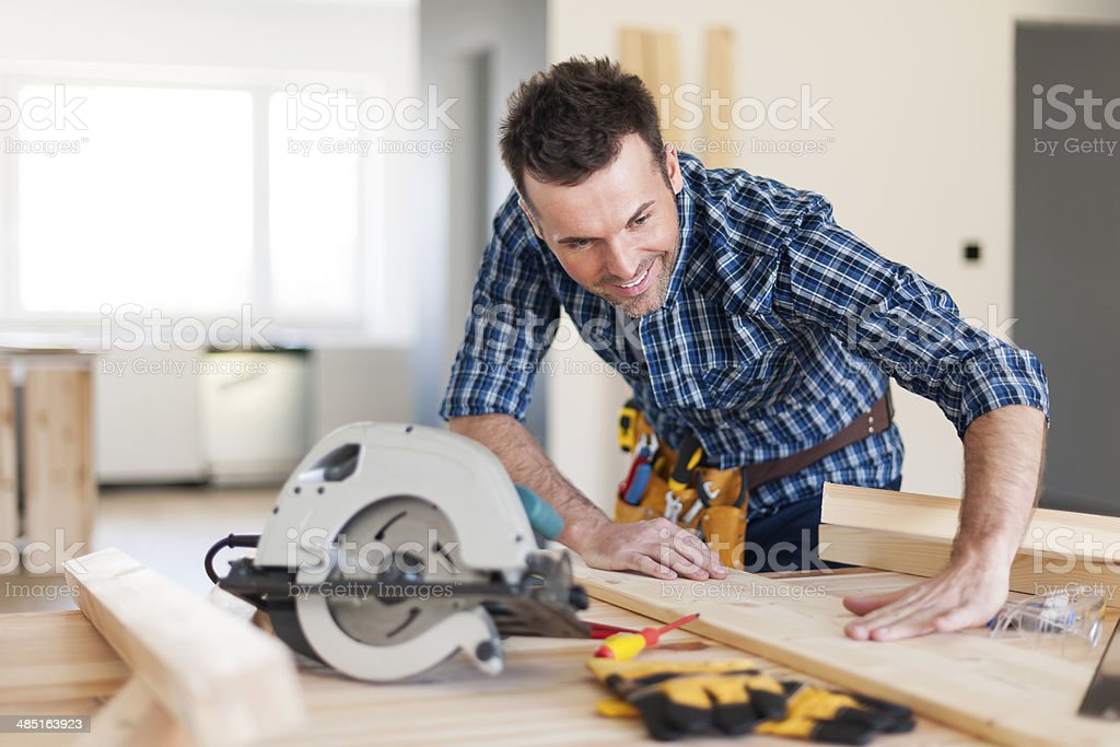 Smiling carpenter checking result of his work stock photo