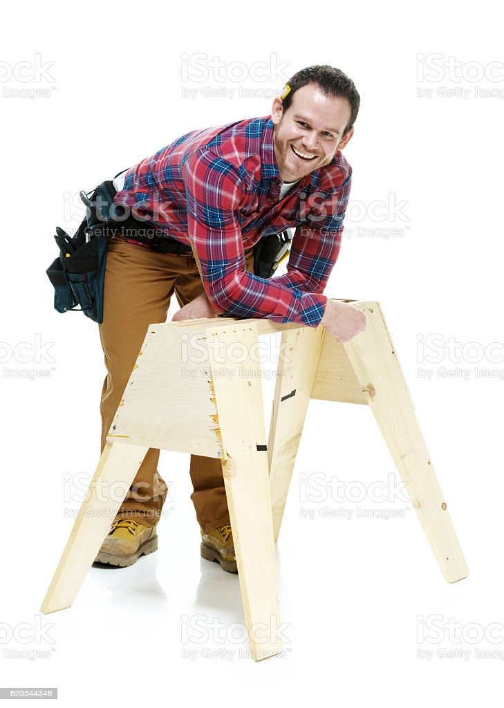 Smiling carpenter leaning on sawhorse stock photo