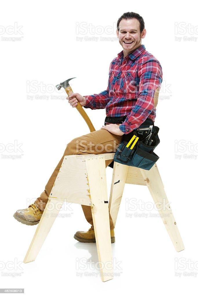 Smiling carpenter sitting on sawhorse royalty-free stock photo