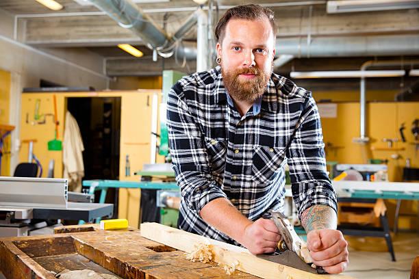 lächelnd schreiner arbeiten mit flugzeug auf holz plank in workshops - baroque tattoo stock-fotos und bilder