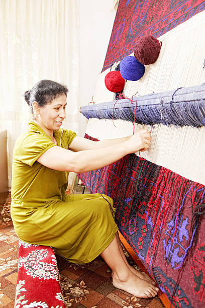 Smiling carpet weaver sideview stock photo
