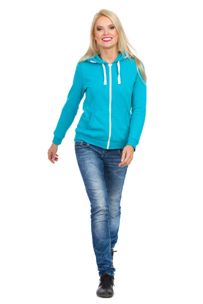 Smiling Casual Blond Woman Is Looking Towards Camera Smiling blond woman in turquoise hoodie and jeans is walking towards camera. Full length studio shot isolated on white. approaching stock pictures, royalty-free photos & images