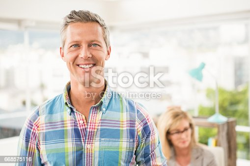 istock Smiling casual businessman in front of his colleague 668575116