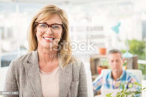 istock Smiling casual businesswoman in front of her colleague 668574962
