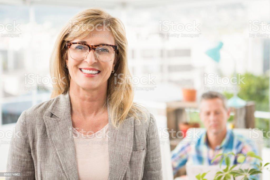 Empresária casual na frente de seu colega a sorrir - foto de acervo