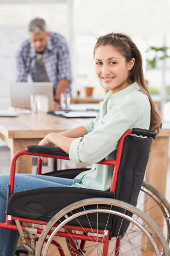 660681964 istock photo Smiling casual businesswoman in wheelchair 668520094