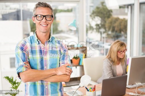 istock Smiling casual designer in front of his working colleague 668575564