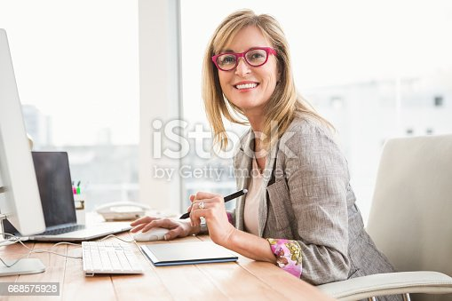istock Smiling casual designer using computer and digitizer 668575928