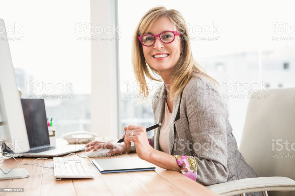 Smiling casual designer using computer and digitizer stock photo