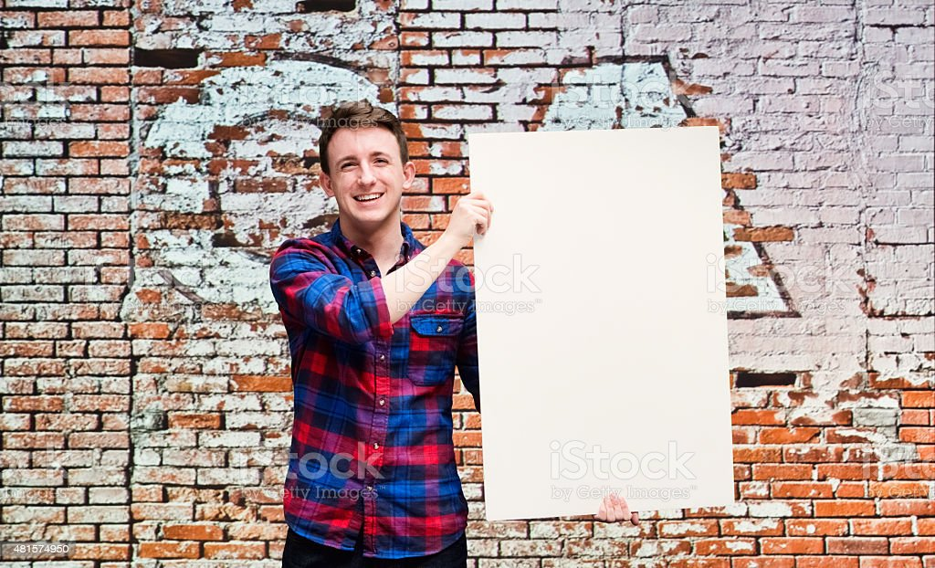 Smiling casual man holding placard stock photo