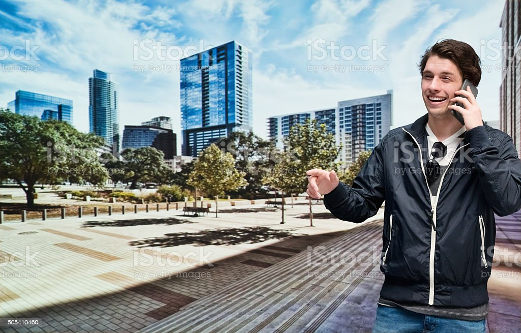 Smiling casual man on mobile outdoors stock photo