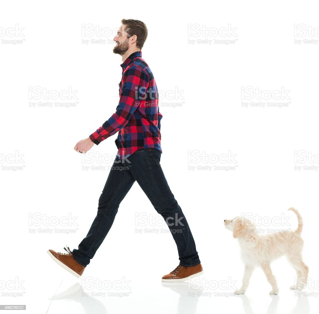Smiling casual man walking with his puppy foto royalty-free