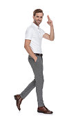 istock smiling casual man with hand in pocket walks and salutes 1131988671