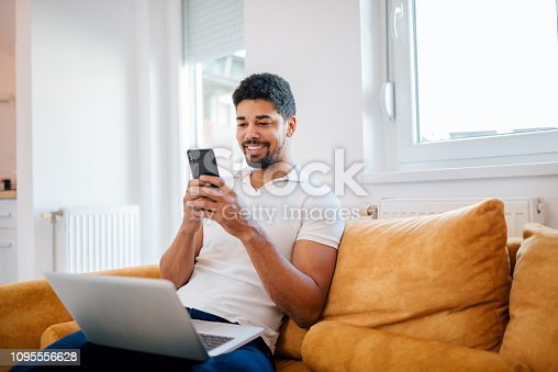 istock Smiling casual mixed-race freelancer using smart phone and laptop while sitting on the sofa. 1095556628