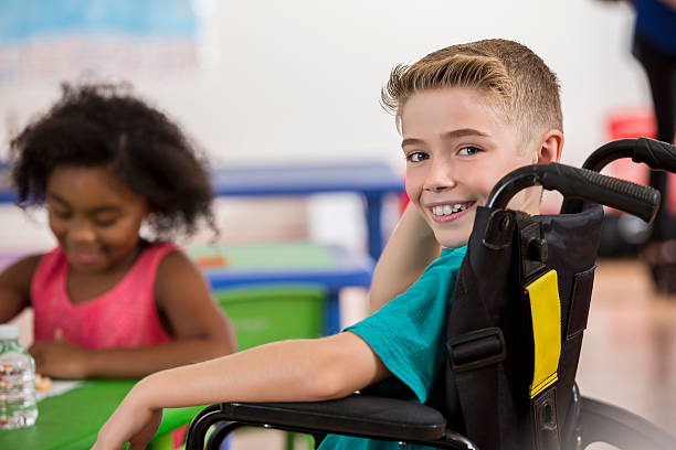 Smiling Caucasian boy in a wheelchair at school stock photo