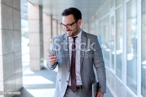 Smiling Caucasian businessman using smart phone and holding tablet in other hand while walking outdoors.