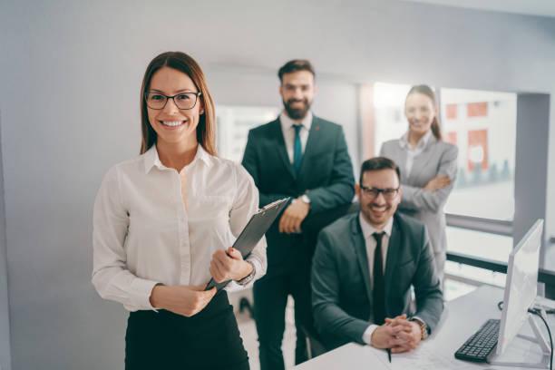 glimlachend kaukasische zakenvrouw in formele slijtage, met brillen en bruin haar bedrijf klembord terwijl staande in het kantoor. in de achtergrond medewerkers glimlachen en poseren. succes business is gebouwd op goede vriendschap. - netherlands map stockfoto's en -beelden