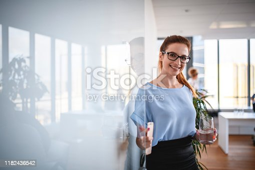 Bespectacled Caucasian businesswoman in mid 20s holding open front door to modern corporate office and looking at camera.