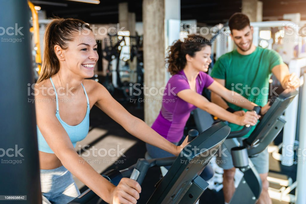 Smiling caucasian female athlete practicing on exercise bike in the...