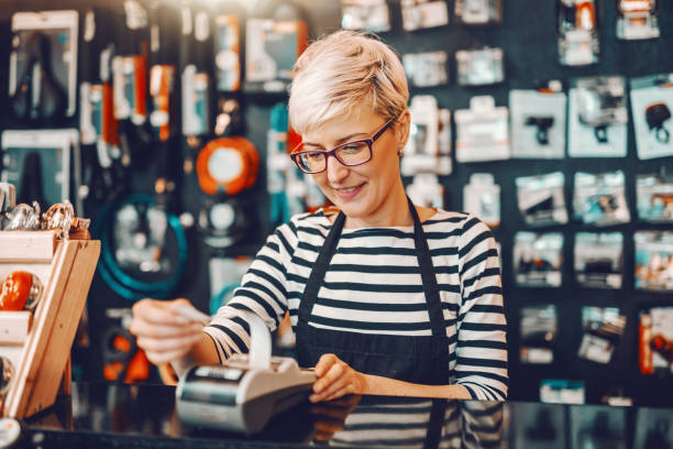Smiling Caucasian female worker with short blonde hair and eyeglasses using cash register while standing in bicycle store. Smiling Caucasian female worker with short blonde hair and eyeglasses using cash register while standing in bicycle store. seller stock pictures, royalty-free photos & images