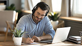 istock Smiling Caucasian man in headphones study on laptop 1276876762