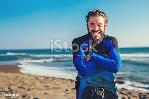 Smiling Caucasian man kitesurfer standing on the beach with his board
