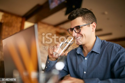 istock Smiling caucasian man with glass of water in hand works with laptop. Businessman in glasses drinks water for body hydration while working. Attractive designer quench thirst. Healthy lifestyle theme 914624876