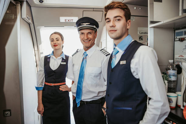 Smiling Caucasian pilot with flight attendants standing on airplane board Attractive stewardess with pilots posing for camera stock photo. Airways concept cabin crew stock pictures, royalty-free photos & images