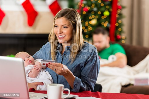 istock Smiling Caucasian woman holding baby and buying Christmas presents online 600413576