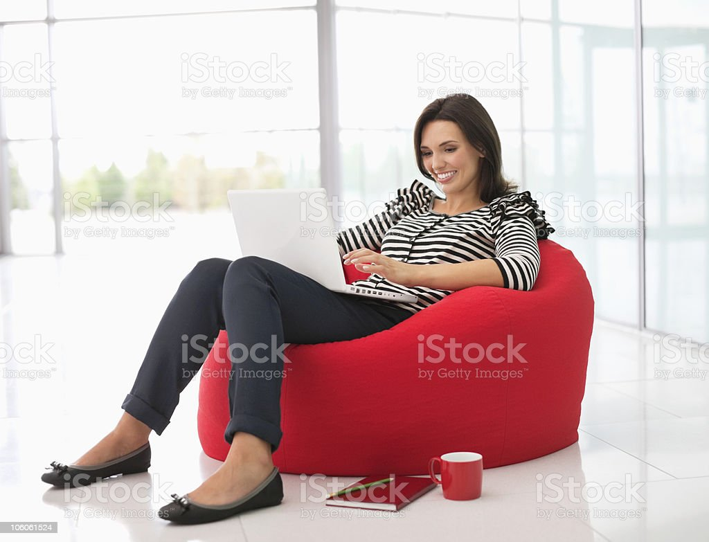 Smiling Caucasian woman sitting on a bean bag with laptop stock photo