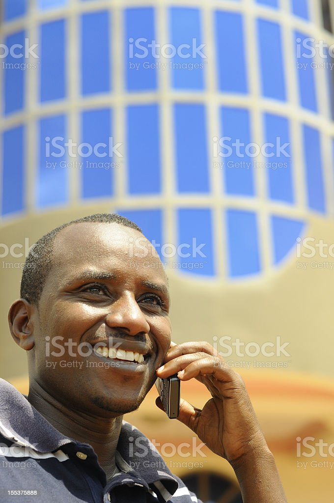 Smiling Central African male using mobile phone stock photo