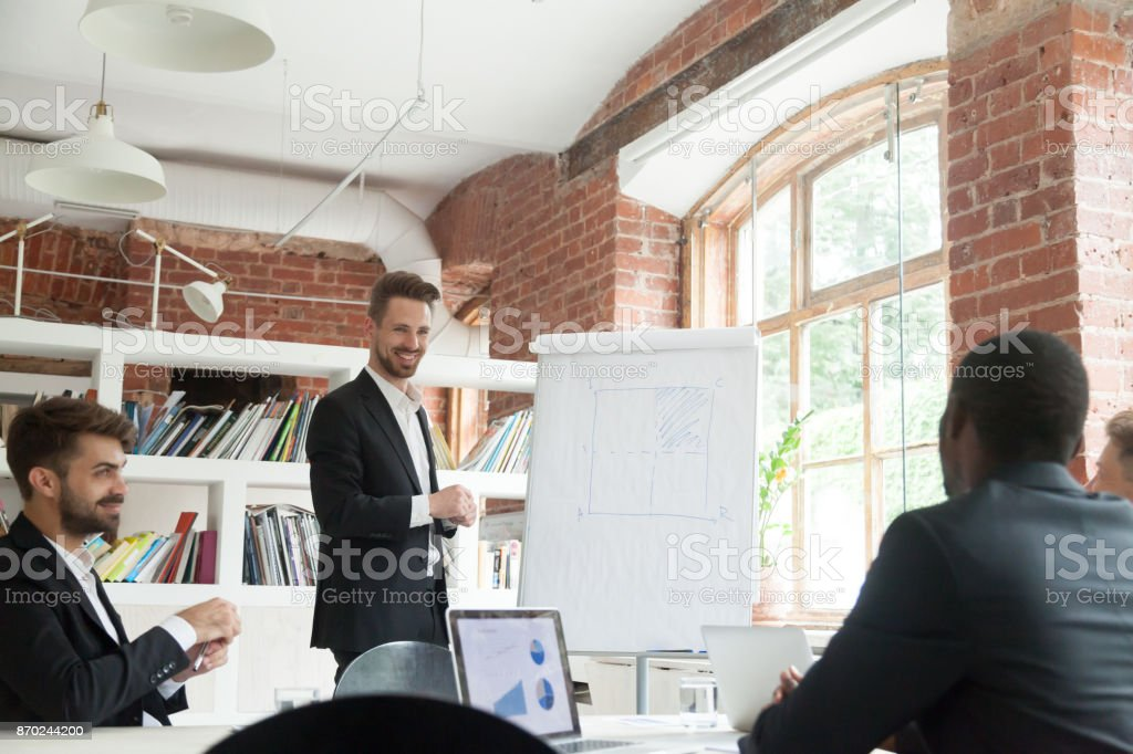 Smiling CEO consulting colleagues about new workflow plan briefing meeting.. stock photo