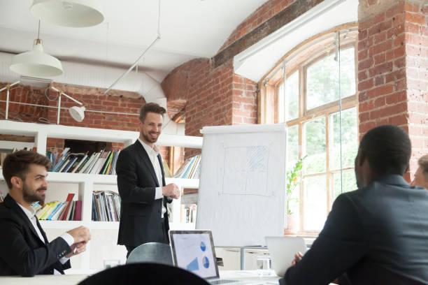 lächelnde ceo consulting kollegen über neue workflow planen briefing meeting... - projektmanager stock-fotos und bilder