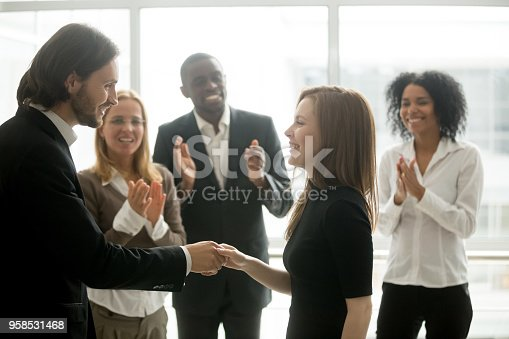istock Smiling ceo handshaking successful female worker showing respect, team applauding 958531468