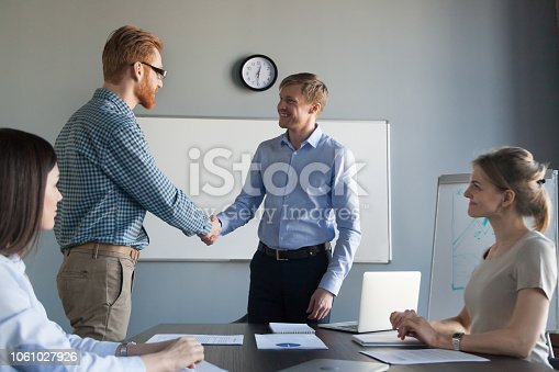 918365170 istock photo Smiling ceo rewarding successful employee with handshake at team meeting 1061027926