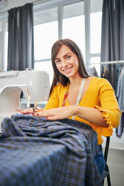 Lächelnd charmante kaukasische Modedesignerin sitzt in ihrem Studio und nähet schöne Abendkleid. – Foto