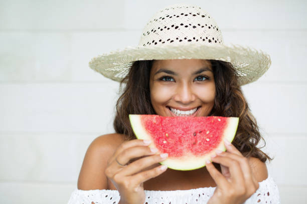 Smiling Charming Woman Eating Slice of Watermelon stock photo